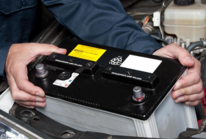 man putting car battery in